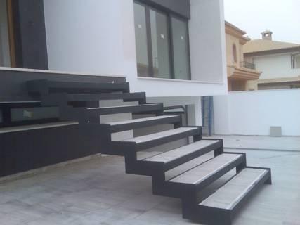 Escalera formada por ménsulas de acero empotradas sobre zanca metálica de elevada rigidez a torsión, anclada en forjados y embutida en cerramiento